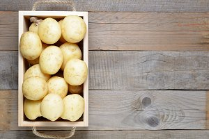 Potatoes in wooden box on table