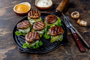 Grilled portobello bun mushroom burgers on cast iron grill pan ob wooden background, top view