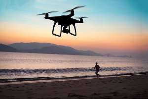 Hovering drone taking pictures of runner at the beach, sunset