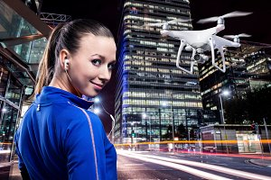 Hovering drone taking pictures of woman running in night city