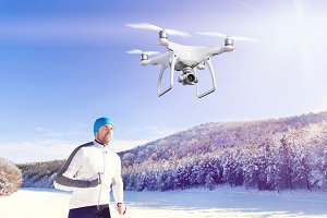 Hovering drone taking pictures of runner in winter nature