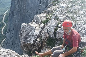 man rock climber sits on the top of the cliff and belays a partner