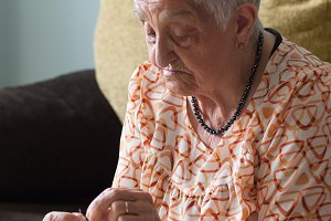 Elderly woman making necklaces