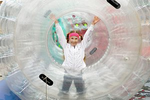 Teen girl happily runs inside a large inflatable cylinder-zorb