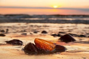 Amber stone on the beach at sunset