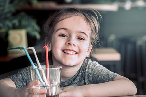 a child drinks a drink from a straw
