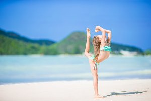Beautiful little girl doing sporty exercises on the beach