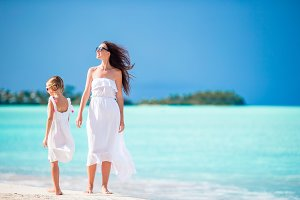 Beautiful mother and her adorable little daughter on the beach
