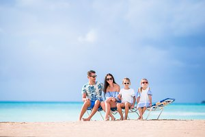 Young beautiful family on white beach