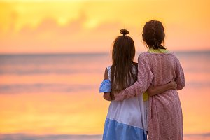 Adorable little girls on the beach with beautiful colorful sunset