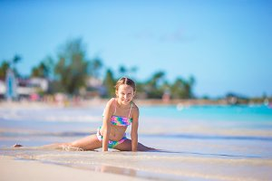 Adorable little girl in shallow water on white beach