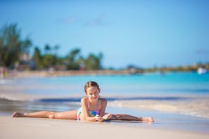 Adorable little girl lying in shallow water on white beach
