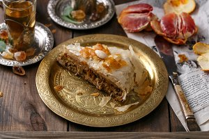 Phyllo pastry chicken pie on copper plate with tea, close view