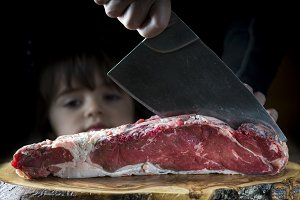 Butcher cutting a piece of meat with a cleaver while a baby girl is looking