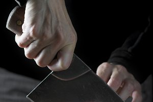 Butcher cutting a piece of meat with a cleaver