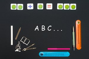 Above stationery supplies and text abc on blackboard