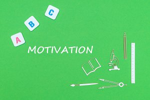 text motivation, from above wooden minitures school supplies and abc letters on green background