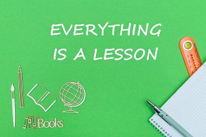 text everyting is a lesson school supplies wooden miniatures, notebook on green background