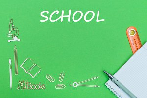 text school, school supplies wooden miniatures, notebook with ruler, pen on green backboard