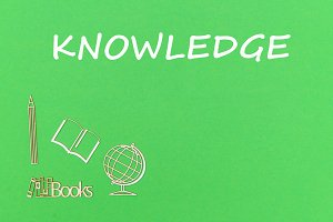 text knowledge, school supplies wooden miniatures on green background