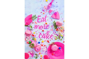 Party concept with Eat more cake paper text, candies, sweets, confetti and macarons. Colorful Birthday celebration flat lay.