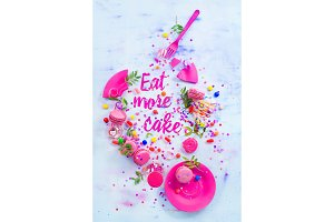 Eat more cake vignette with paper text, candies, sweets, confetti and macarons. Colorful Birthday celebration flat lay. Party concept in high key.