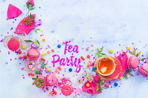 Tea party concept with paper text, candies, sweets, confetti, macarons and dynamic tea splash. Colorful Birthday celebration flat lay with copy space.
