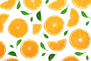 Slices of orange or tangerine decorated with green leaves isolated on white background, top view. Fruit composition