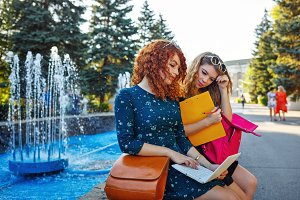Two female students sit at fountain