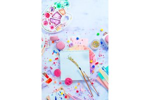 Painting with sweets party concept, artist tools, brushes and palette in a colorful creative flat lay with macarons and candies.