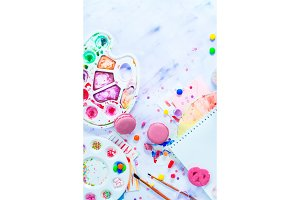 Pink macarons in a colorful party activity concept with confetti, artist tools, brushes, palette and sketchbook with blank pages. Creative celebration flat lay with copy space.
