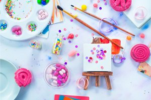 Tiny easel with confetti, pink macarons, candies, brushes and watercolor color wheel. Sweettooth artist tools creative party concept.