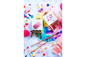 Tiny easels with confetti, pink macarons, candies, brushes and watercolor color wheel. Sweettooth artist tools creative party concept.