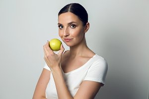 young girl in a white t-shirt with an apple