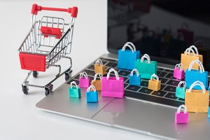 miniature shopping bags on laptop