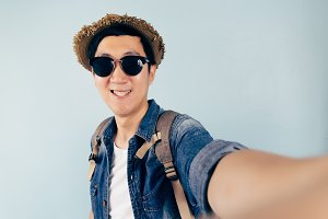 Young Asian tourist smiling and taking a selfie isolated over pastel blue background