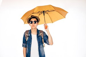 Young Asian tourist holding umbrella isolated over white background. Alone and Looking for partner to travel