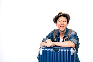 Young Asian tourist with hat smiling and putting arms on travelling luggage isolated over white background