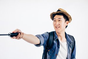 Young Asian tourist with hat smiling and holding selfie stick taking a selfie photo isolated over white background