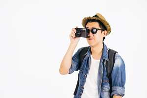 Young Asian tourist with hat and sunglasses smiling and holding camera isolated over white background