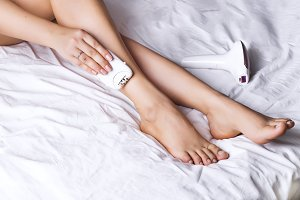 Woman using laser epilator for hair removal procedure at home