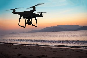Silhouette of hovering drone taking pictures of the beach at sun