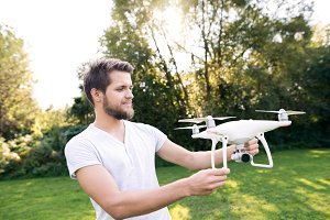 Young hipster man holding drone. Sunny green nature.