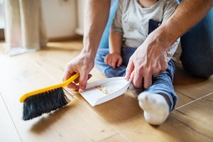 Unrecognizable father and toddler with brush and dustpan.