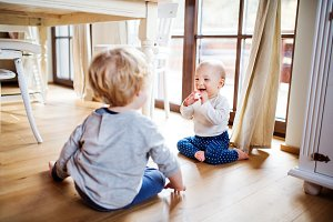 Two toddler children playing at home.