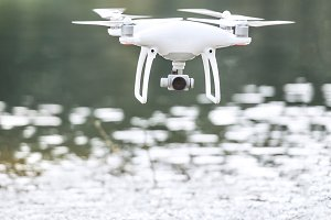 Drone quadcopter with camera flying above water.