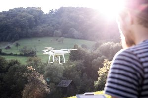 Unrecognizable hipster man with flying drone. Sunny nature.
