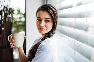 Woman by the window holding cup of coffee.