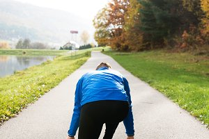Runner at the lake on asphalt path in steady position