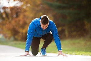 Young runner in park on asphalt path in steady position